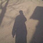 我的影子,左手拿着面包和奶茶,右手举着手机在照相